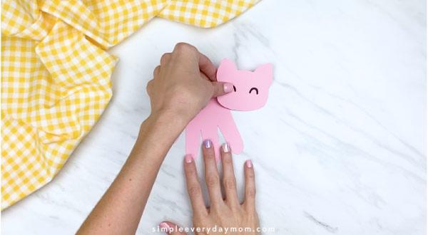 Hands gluing pig head onto handprint pig craft