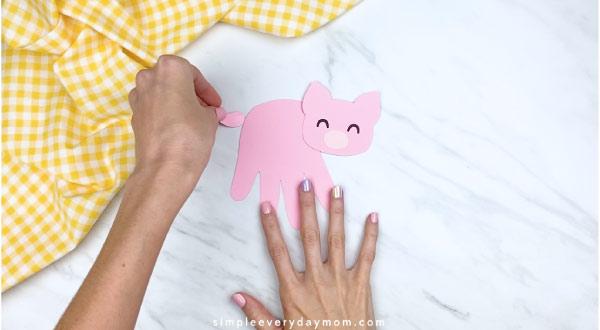 Hands gluing tail onto handprint pig craft