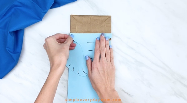 Hands gluing paper elephant trunk to paper bag