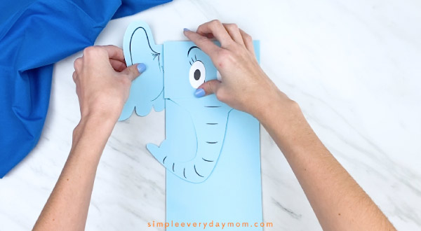 Hands gluing ears to back of Horton paper bag craft