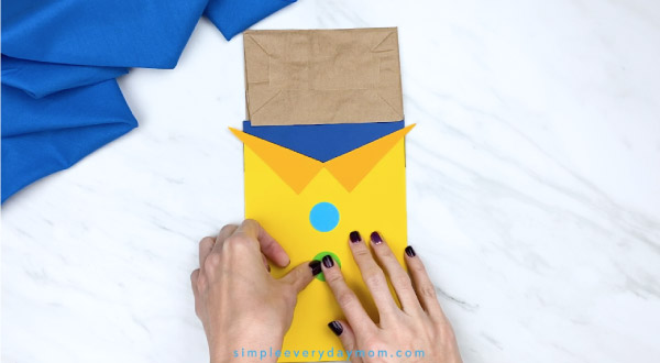 hands gluing buttons onto paper Pete the Cat puppet