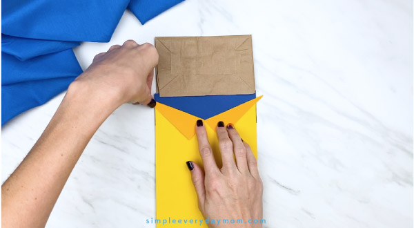 hands gluing collar onto paper bag Pete the Cat