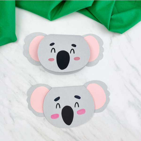 two homemade koala cards with marble background and green fabric