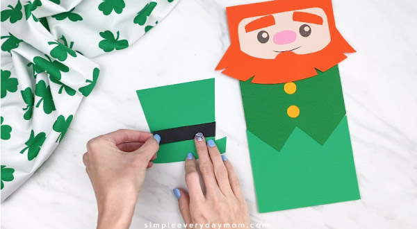 Hands gluing hat band onto leprechaun hat