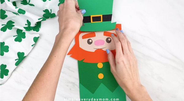 Hands gluing leprechaun hat onto paper bag leprechaun craft
