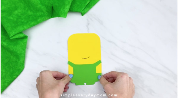 Hands gluing green overall to paper minion