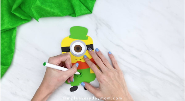 Hands drawing pocket onto minion leprechaun overalls