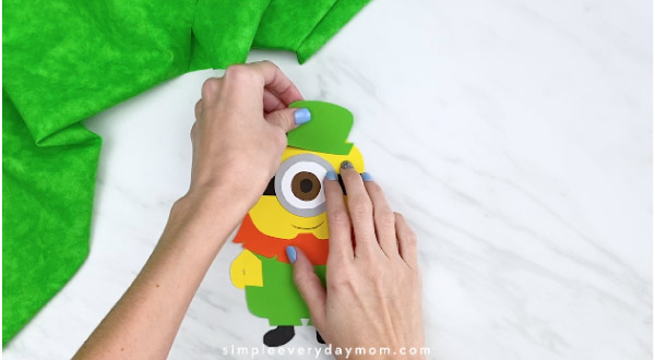 Hands gluing hat onto paper leprechaun minion