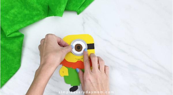 Hands gluing eye onto paper leprechaun minion