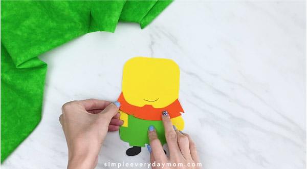 Hands gluing beard onto leprechaun minion craft
