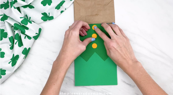 Hands gluing buttons onto paper bag leprechaun