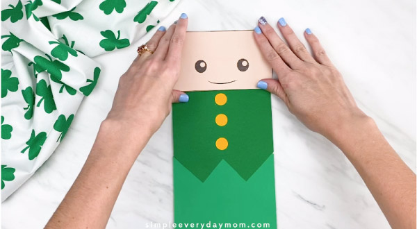 Hands gluing leprechaun face onto paper bag