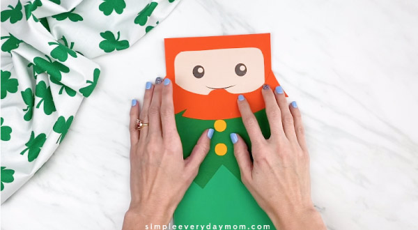 Hands gluing beard onto paper bag leprechaun craft