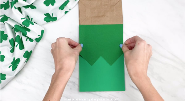 Hands gluing green vest onto paper bag