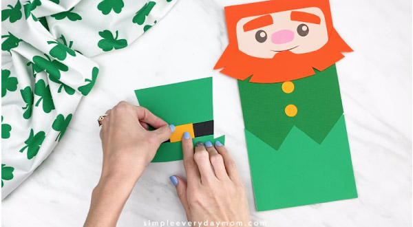 Hands gluing leprechaun hat buckle on