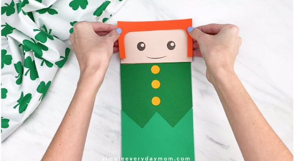 Hands gluing hair onto paper bag leprechaun craft