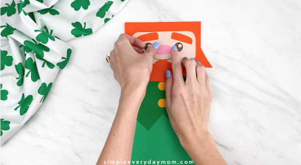 Hands gluing nose onto paper bag leprechaun craft