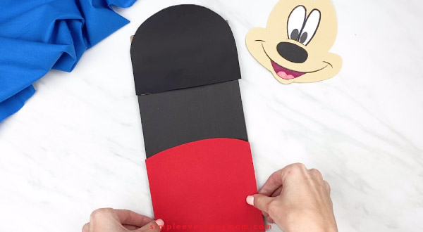 hands gluing mickey pants onto paper bag