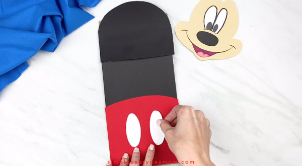 hands gluing buttons onto mickey mouse pants