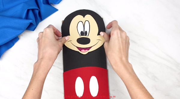 hands gluing mickey mouse face onto paper bag craft