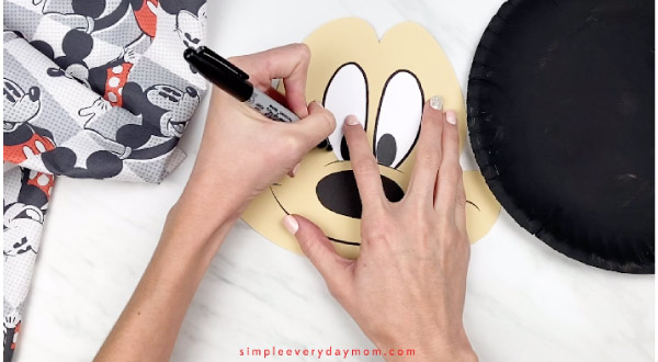 hands outlining Mickey\'s eyes with black marker