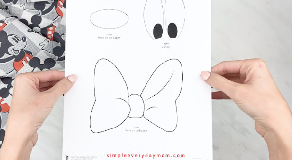 hands holding Mickey Mouse craft template