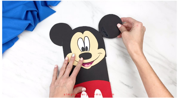 hands gluing mickey ears onto mickey mouse craft