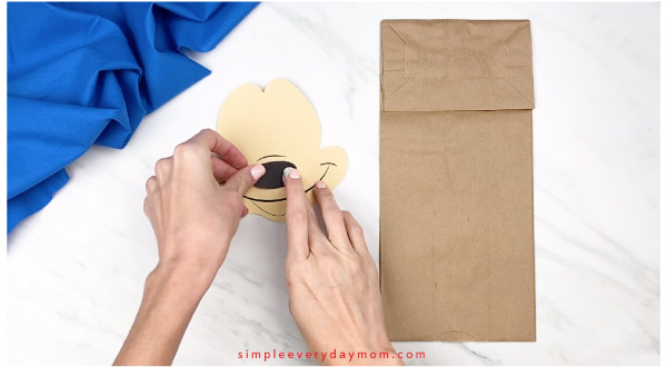hands gluing nose onto paper mickey mouse craft