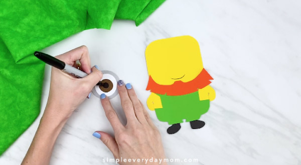 Hands drawing pupil on paper minion eye