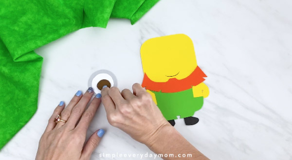 Hands gluing paper minion eye together