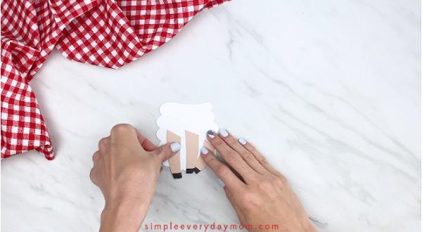 Hands gluing legs onto sheep card craft