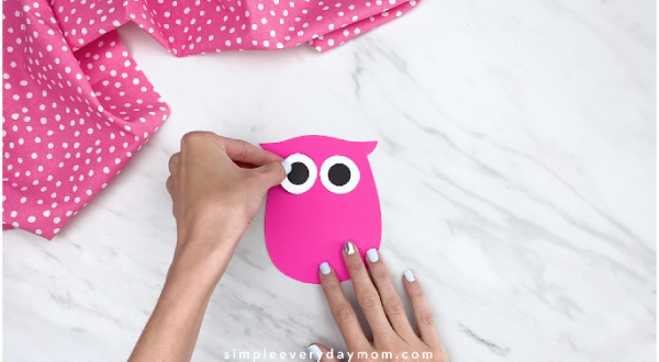hands gluing on eyes to pink paper owl