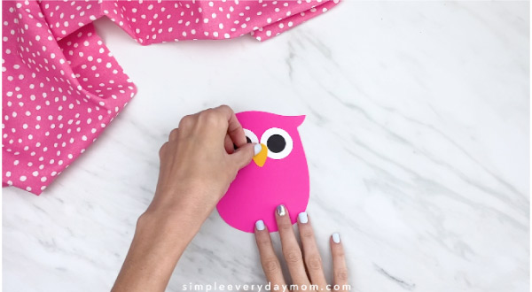 hand gluing beak onto pink paper owl