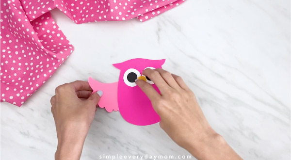 hands gluing on wing to pink paper owl