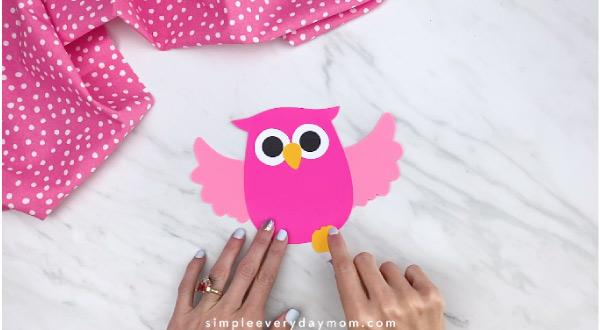 hand gluing feet onto pink paper owl