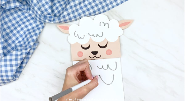 Hands drawing fluff lines onto paper bag sheep craft