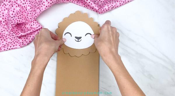 hands gluing llama face onto paper bag