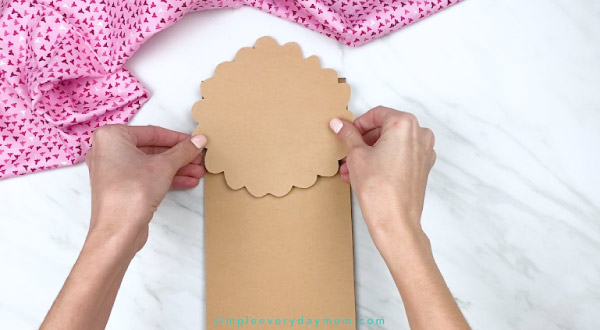 hands gluing paper onto brown paper bag