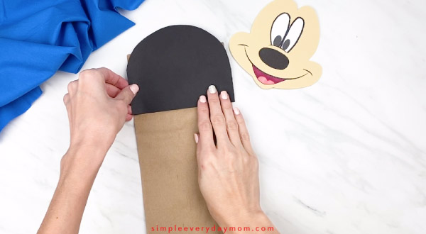 hands gluing paper mickey head onto paper bag craft