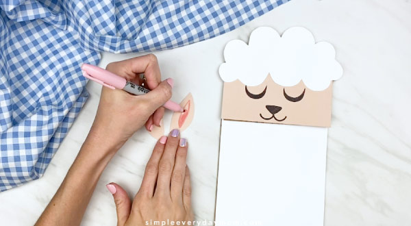 Hands drawing inner ears onto sheep craft ears