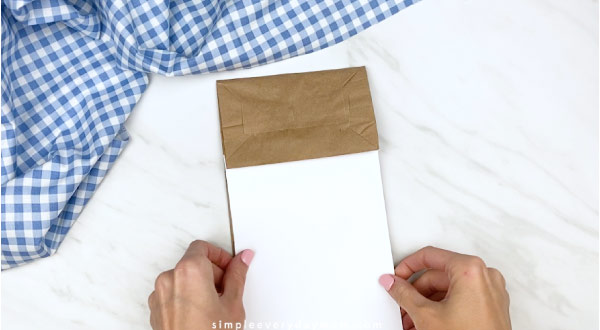 Hands gluing white paper onto paper bag