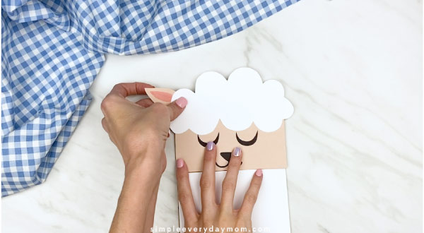 Hands gluing ears to back of paper bag sheep craft