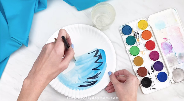 Hands painting water onto paper plate