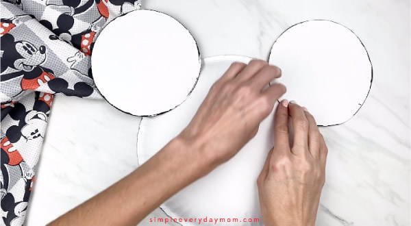 hands taping Mickey Mouse ears to back of paper plate Mickey