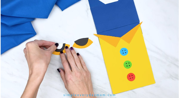 hands assembling paper Pete the Cat eyes