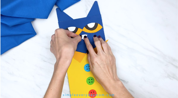 hands gluing nose onto paper bag puppet craft
