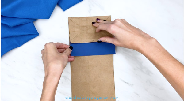 hands gluing blue onto paper bag Pete the Cat