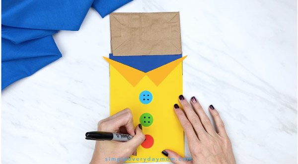 hands drawing button holes on paper bag Pete the Cat