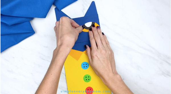 hands gluing paper Pete the Cat eyes onto puppet craft