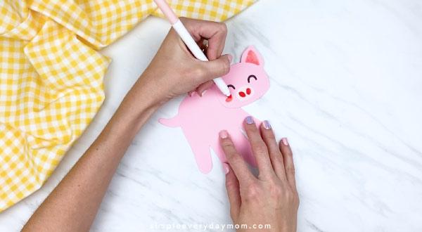 Hands drawing cheeks onto handprint pig